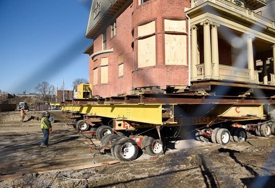 Workers prepare to move the David Mackenzie House to its new location on Wayne State University's campus.