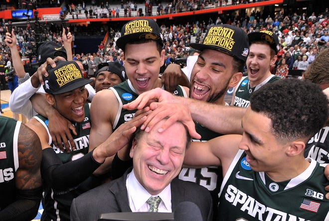 """The Spartans mess up coach Tom Izzo's hair in celebration as Michigan State  beats Louisville, 76-70, in their 2015 NCAA """"Elite Eight"""" game in Syracuse, N.Y."""