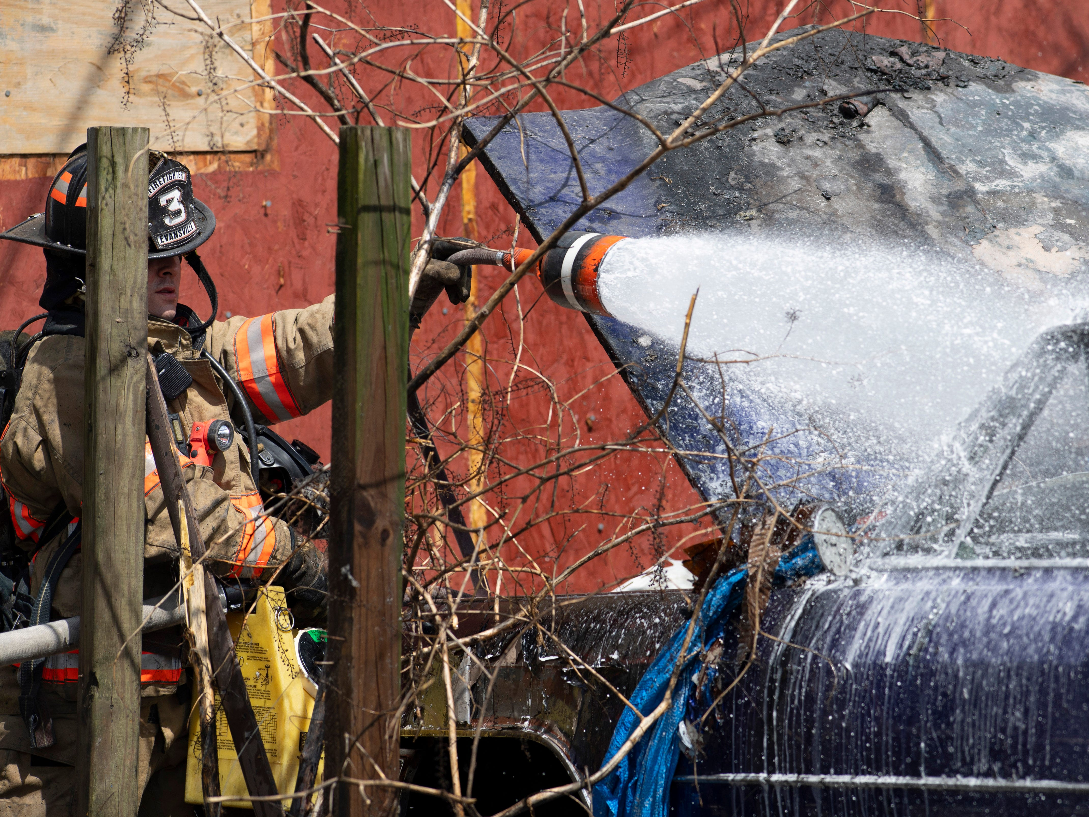 Firefighter Dominic Turi with Fire Station 3 puts foam on the remains of a 1963 Cadillac behind a home at 1904 Indiana Street Monday afternoon. The siding of the rear of the home was torn off to make sure the fire hadn't crept into the house. Evansville Fire Department believes the blaze started as a trash fire. Nobody was injured in the fire.
