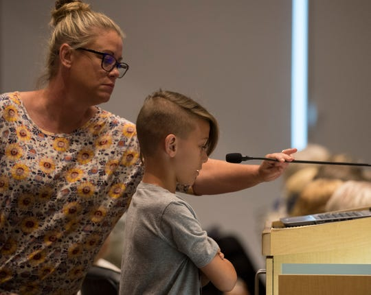 Erin Diaz adjusts the microphone for her son Colin, 10, who was addressing the Cape Coral city council Monday afternoon, 4/1/19, during a public meeting.