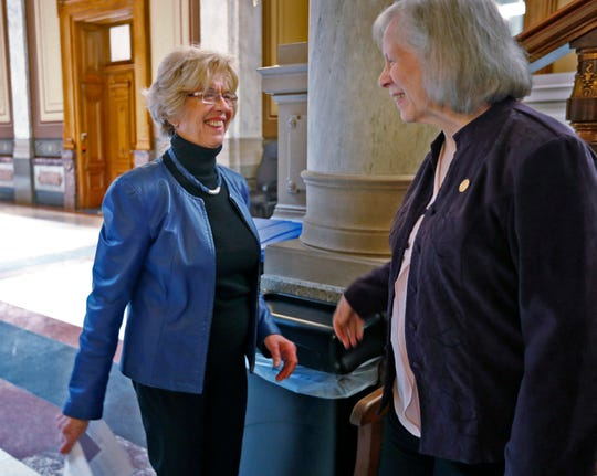 State Rep. Sue Errington smiles to Rep. Pat Boy during a rally at the Statehouse on April 1, 2019.