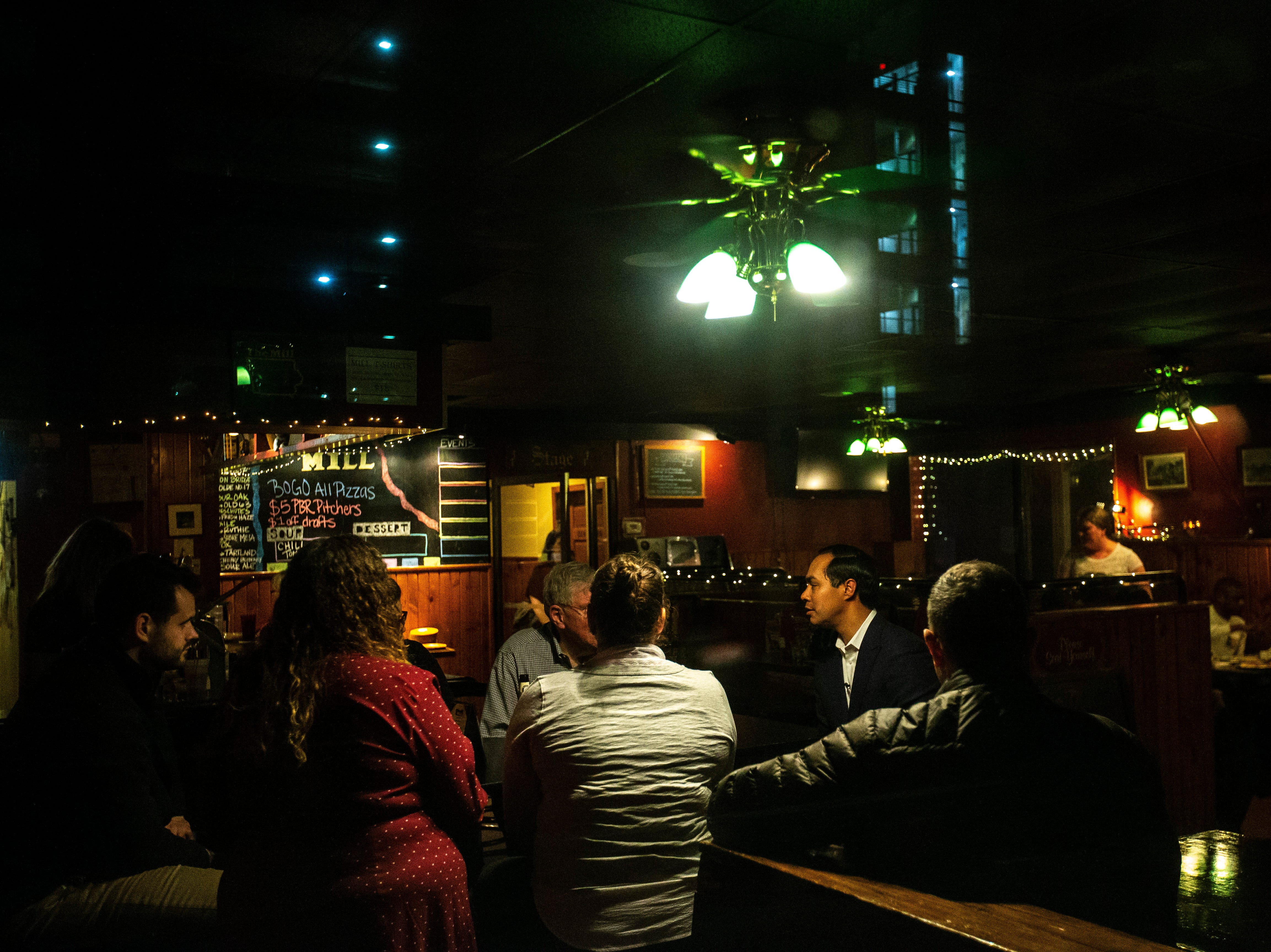 Democratic presidential candidate Julián Castro speaks with Bob Dvorsky, Sen. Zach Wahls, D-Coralville, and other locals after a Lotería game night hosted by LULAC Council 308 on Sunday, March 31, 2019, at The Mill in downtown Iowa City, Iowa.