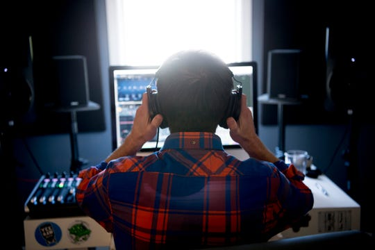 Matt Honkonen puts on his headphones while working in his home studio in the Bearden area of Knoxville, Tennessee on March 27, 2019. Pitchwire, a startup, produces custom music and sound design for all types of visual and audio projects.