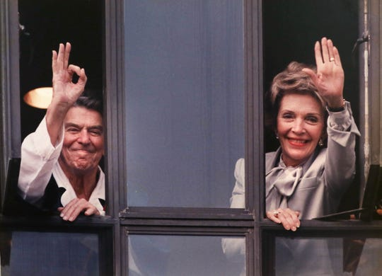 President Ronald Reagan and first lady Nancy Reagan wave from a Bethesda Naval Hospital window after the president was treated for cancer in 1985.