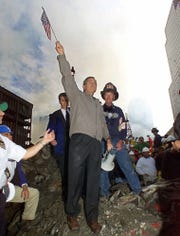 In this Sept. 14, 2001, photo, as rescue efforts continue in the rubble of the World Trade Center in New York, President Bush raises an American flag while standing on a burnt fire truck in front of the World Trade Center during a tour of the devastation. Firefighter Bob Beckwith is at right. Accompanied by New York Mayor Rudolph Giuliani and other New York politicians, Bush toured the disaster site on foot after getting a helicopter view of the devastation.