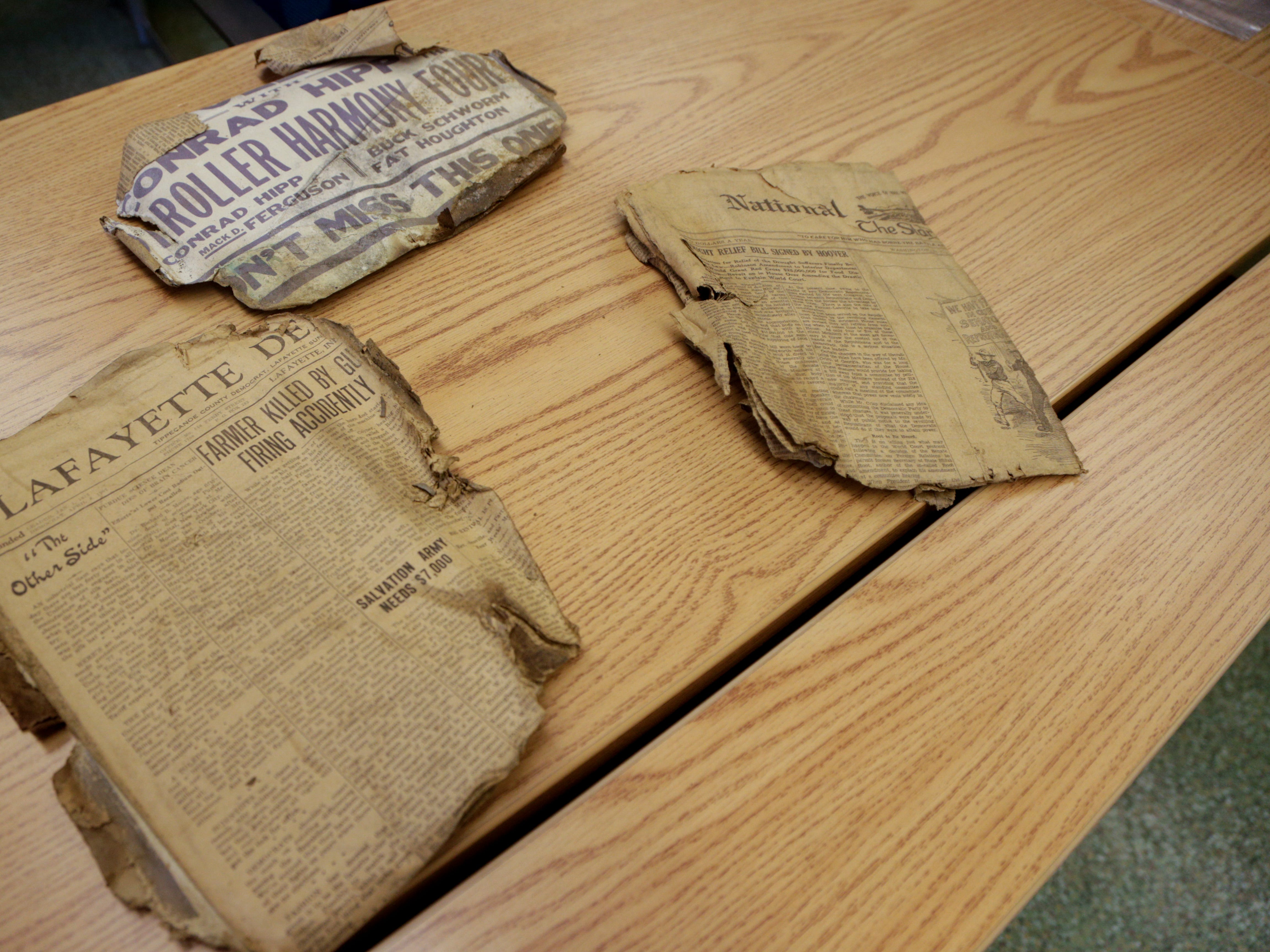 Newspaper clippings from January 26, 1931 sit on a table after being removed from a time capsule, Monday, April 1, 2019, at the Tippecanoe County Historic Association in Lafayette. The copper box, unearthed on March 28, 2019 under a boulder that commemorated the Spanish-American War in front of the Columbian Park Zoo, contained several newspaper clippings and a list of names.