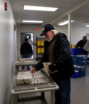 Nick England, a volunteer driver for Fairfield County Meals on Wheels and Older Adult Services, organizes meals he's delivering Monday, April 1, 2019, at the group's new location in the former Cedar Heights Elementary in Lancaster.