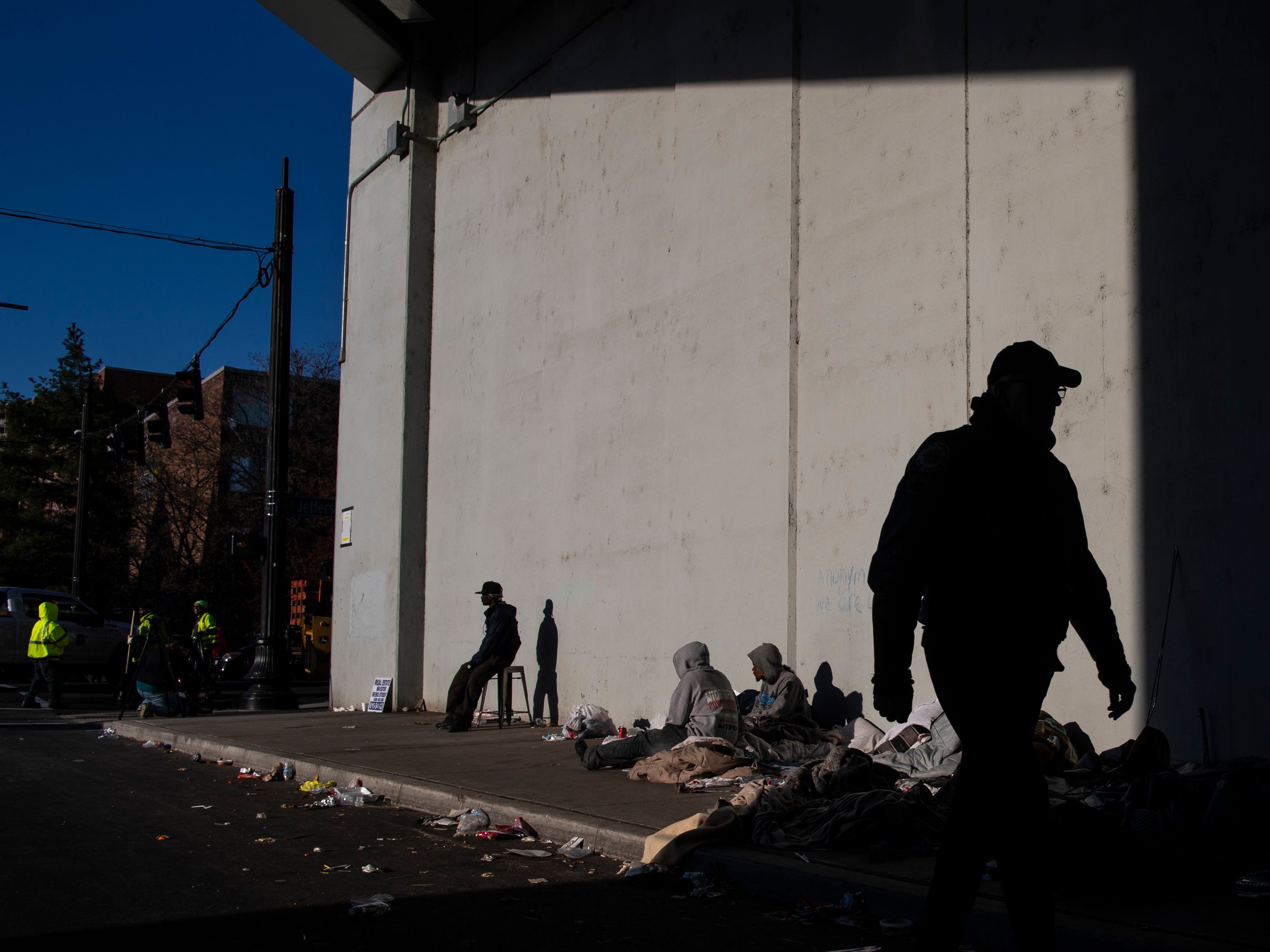 Louisville homeless residents hang out along Jackson Street as Louisville city crews clean out the camp at the intersection of Jackson and Jefferson streets Monday morning. April 1, 2019