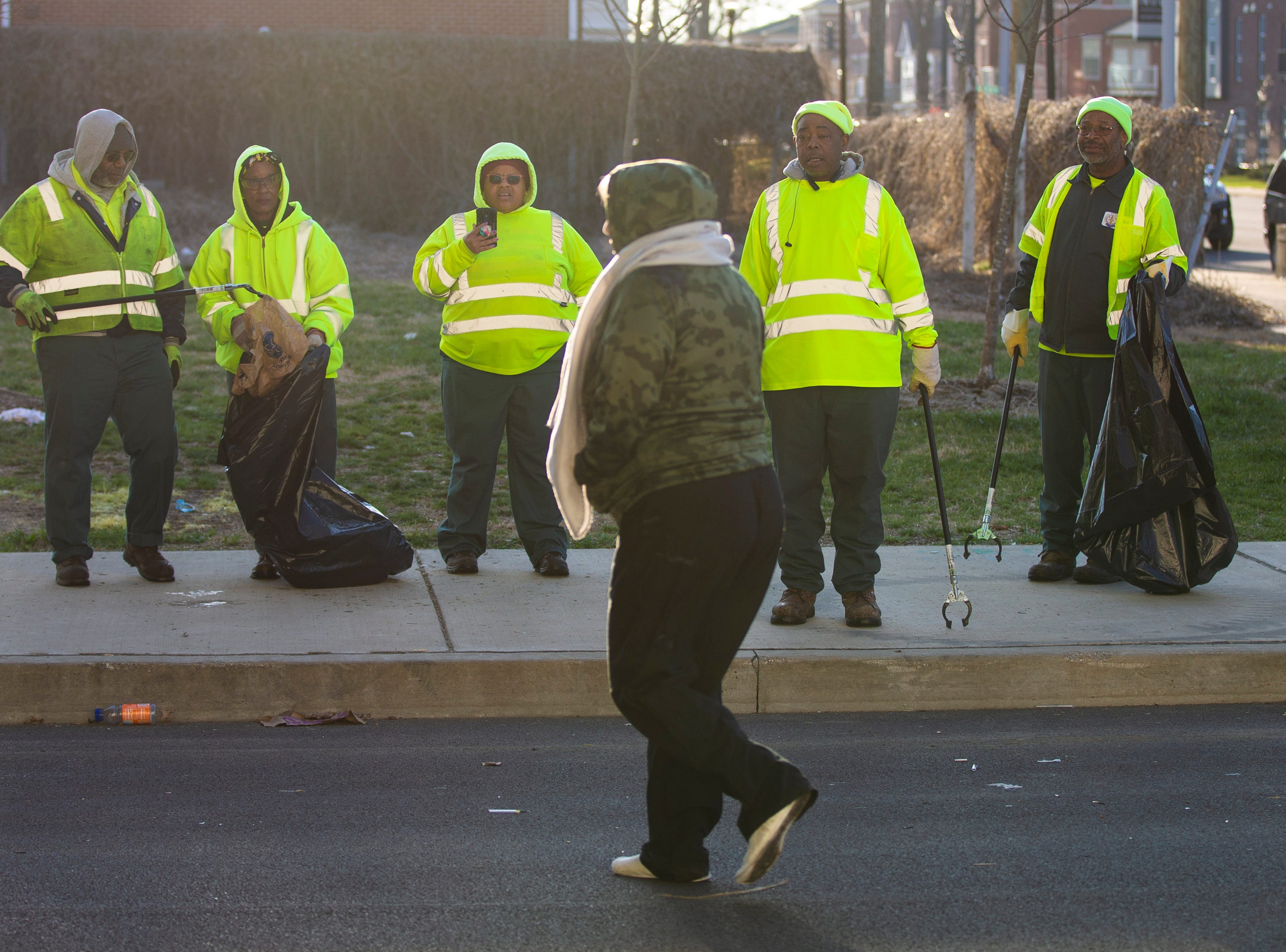 Homeless residents walk past as city crews cleaned out the homeless camp at the intersection of Jackson and Jefferson streets Monday morning.  April 1, 2019