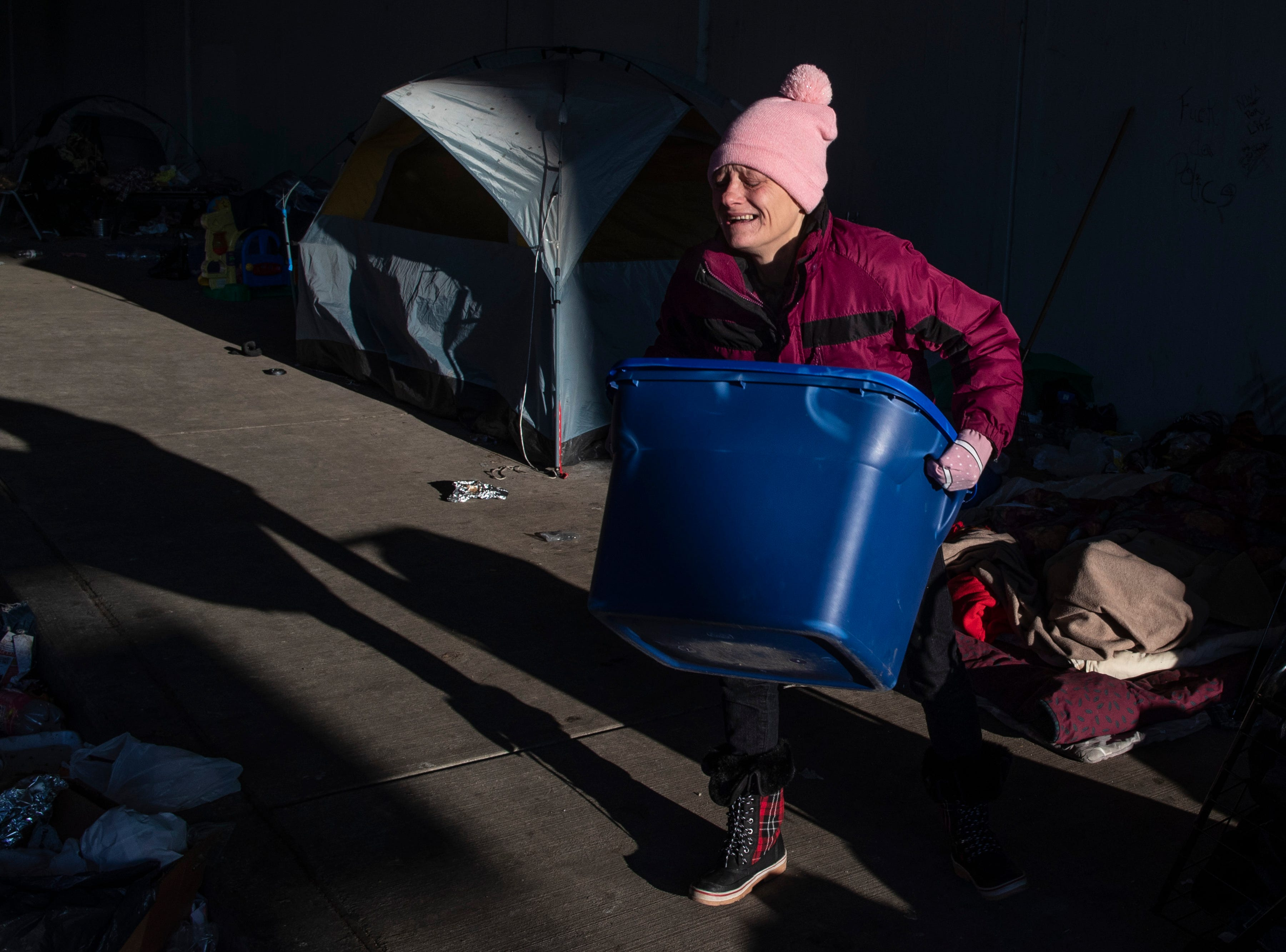 Karen Colmore struggles to pack up her belongings as city crews cleaned out the homeless camp at the intersection of  Jackson and Jefferson streets Monday morning. April 1, 2019