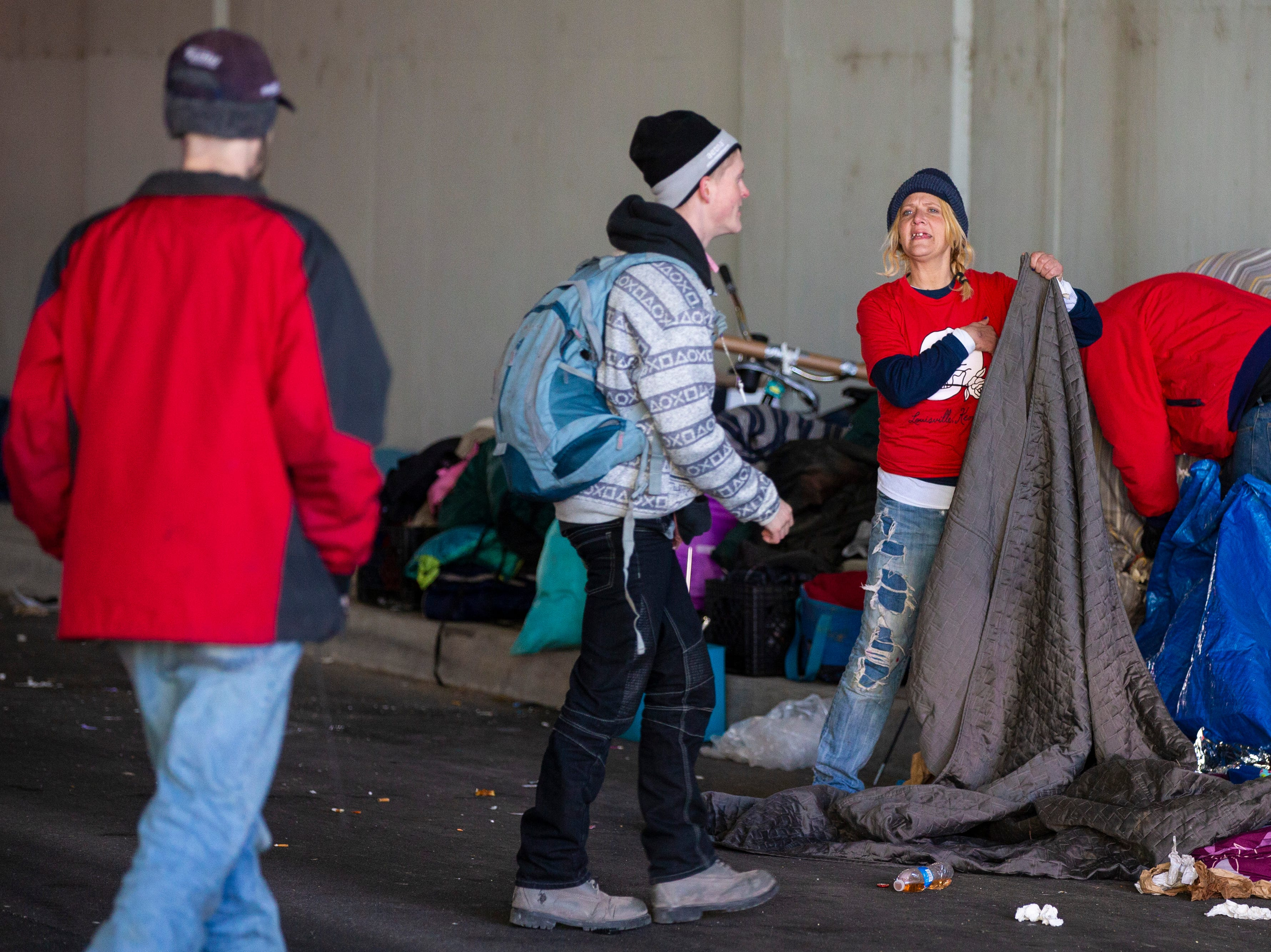 Dani Crisp, right, collects her family's belongings as city crews cleaned out the homeless camp at the intersection of Jackson and Jefferson streets Monday morning. April 1, 2019