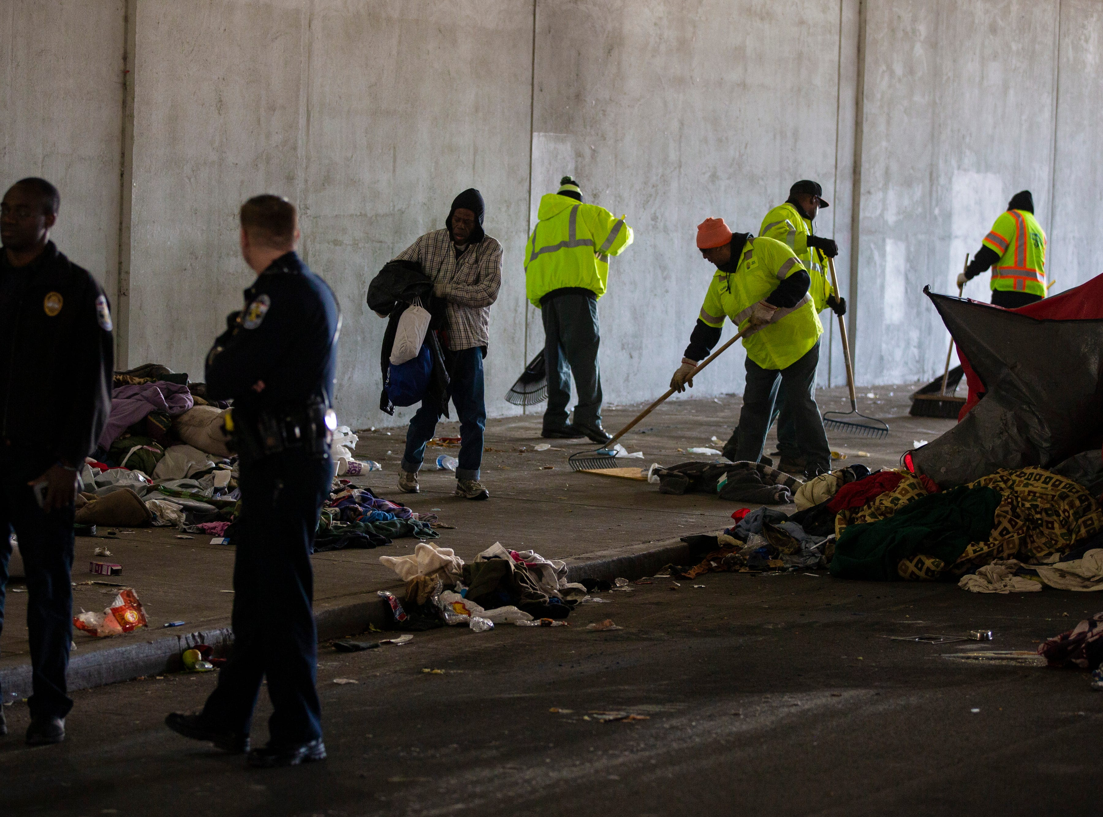 Police look on as Louisville city crews clean out the homeless camp at the intersection of Jackson and Jefferson streets Monday morning. April 1, 2019