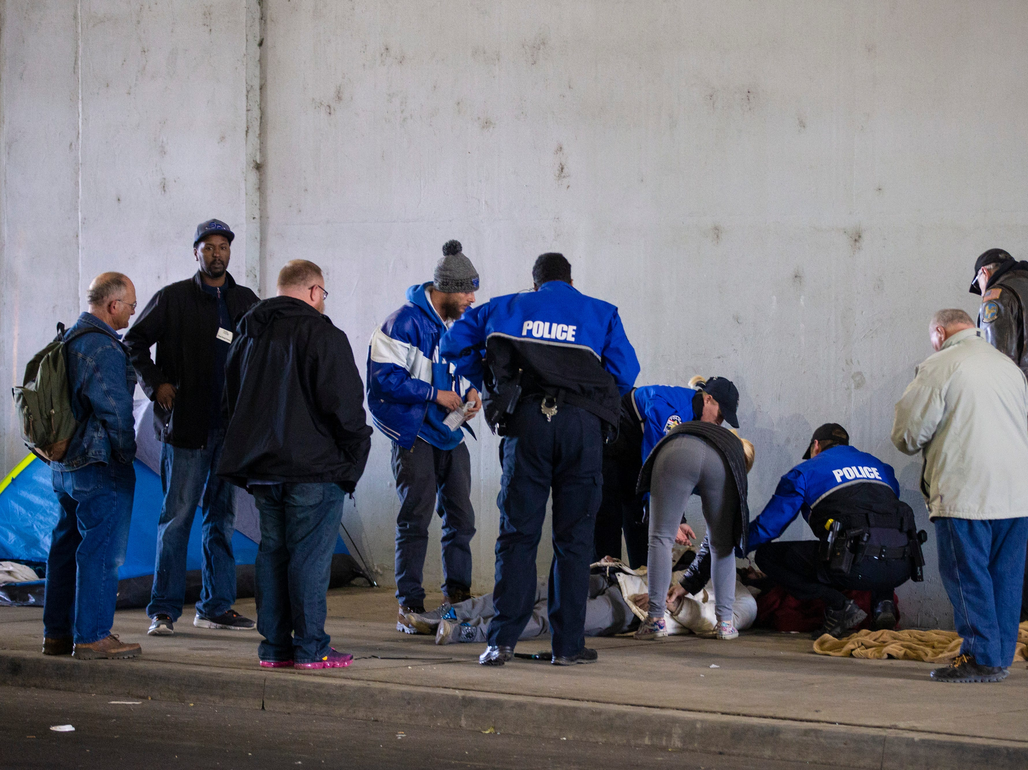 Police and EMS employees check in on a reported overdose as city crews cleaned out the homeless camp at the intersection of Jackson and Jefferson streets Monday morning.  April 1, 2019