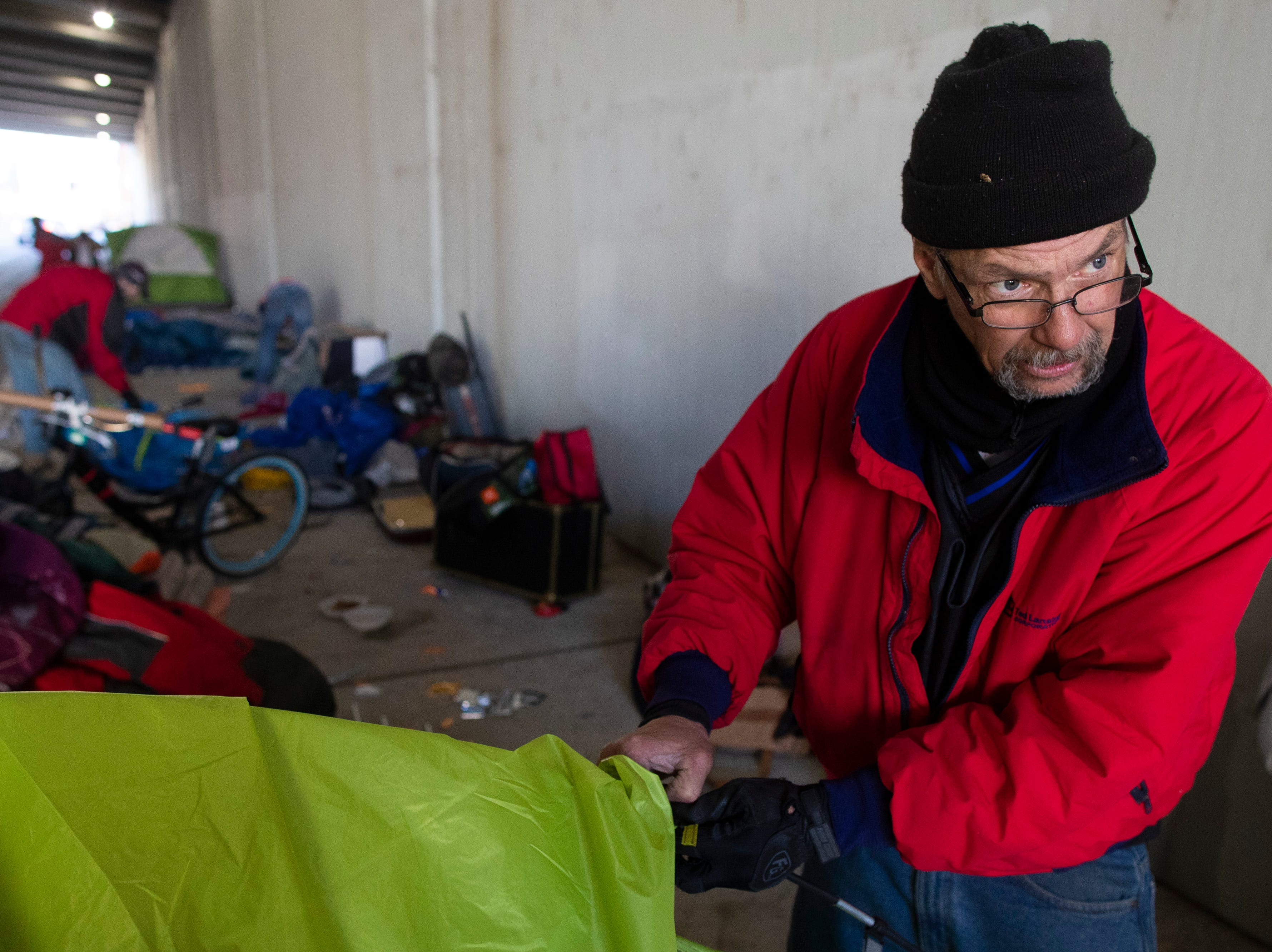 Jeff Weston packs up his family's belongings as Louisville city crews clean out the homeless camp at the intersection of Jackson and Jefferson streets Monday morning.  April 1, 2019