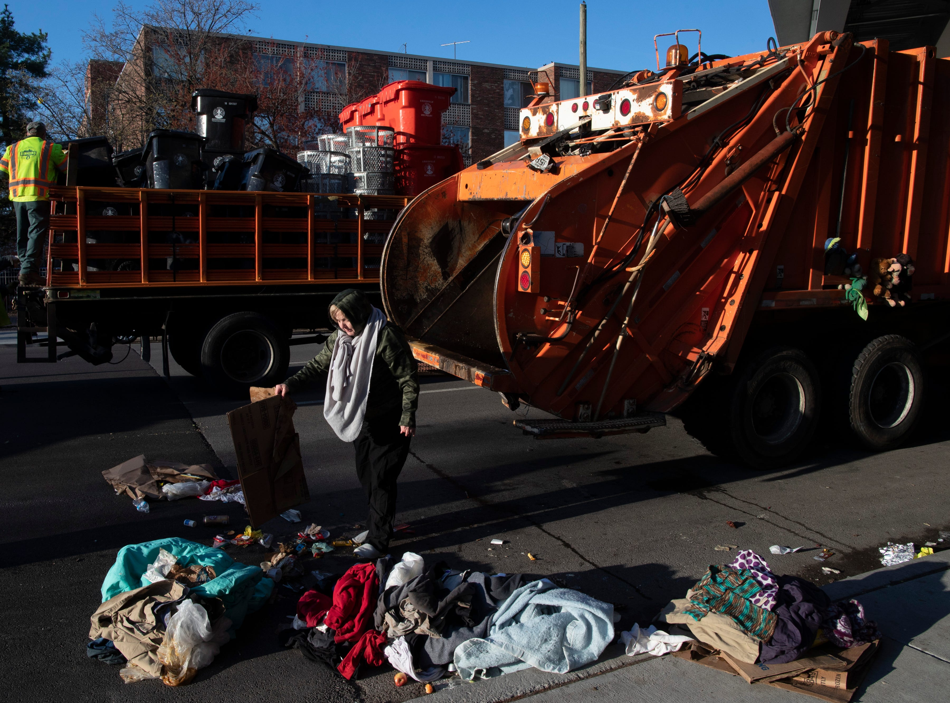 Paula Rae Russell Hunt goes through her things Louisville city crews clean out the homeless camp at the intersection of Jackson and Jefferson streets Monday morning. April 1, 2019
