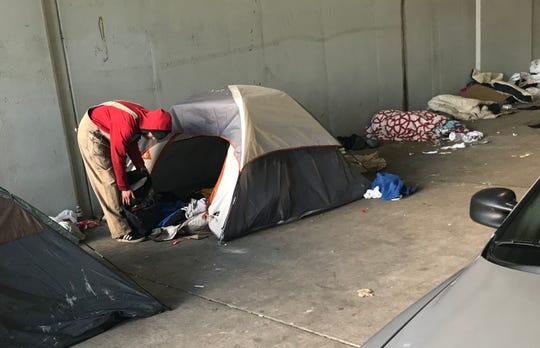 A homeless man packs up his gear before city workers destroy the homeless camp where he lived.