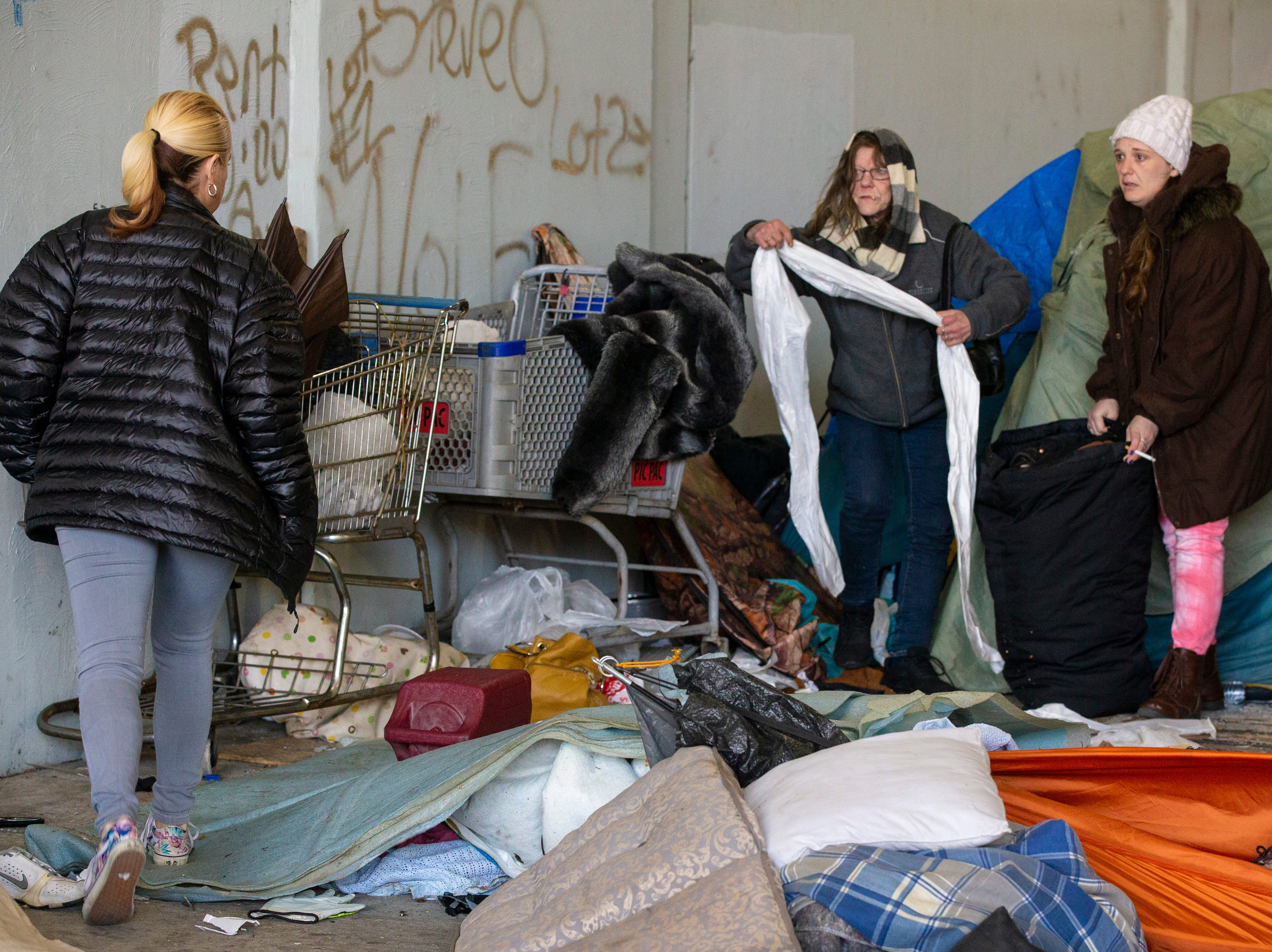 Homeless residents work on packing their belongings as city crews cleaned out the homeless camp at the intersection of Jackson and Jefferson streets Monday morning. April 1, 2019