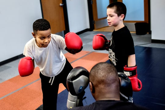Boxing trainer Kolmarge Harris, center, works with Dwaine Maybin Jr., 7, left, and Enicio Montalvo, 8, during a class on Thursday, Feb. 7, 2019, at Harris' gym in Old Town Lansing. Harris, a retired professional boxer, offers training for adults and kids with a focus on children who face taunting and bullying like he experienced as a youth.