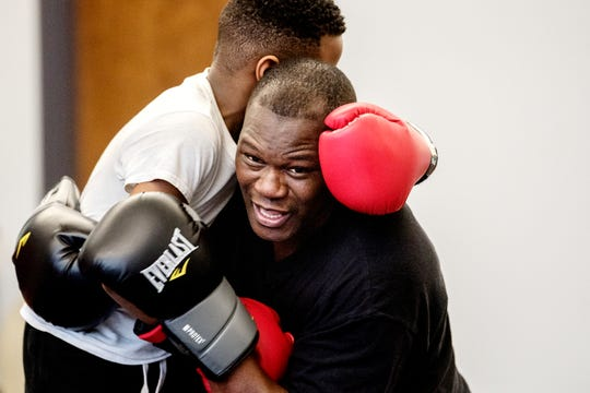 Boxing trainer Kolmarge Harris, right, works with Dwaine Maybin Jr., 7, left, on boxing skills on Thursday, Feb. 7, 2019, in Old Town Lansing. Harris, a retired professional boxer, offers training for adults and kids with a focus on children who face taunting and bullying like he experienced as a youth.