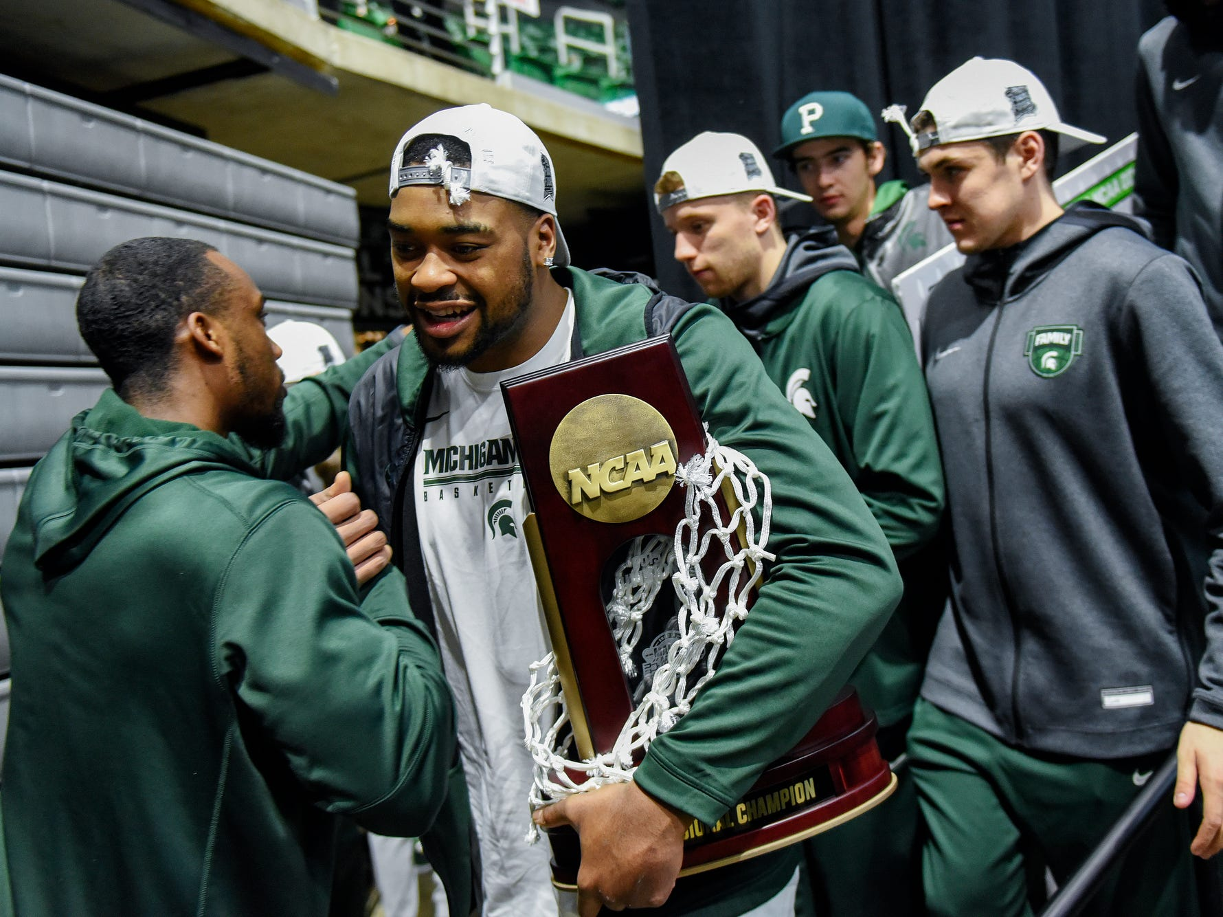 Michigan State's Nick Ward holds the East Regional Championship trophy as he and the team leave the stage during a rally after MSU's victory over Duke on Sunday, March 31, 2019, at the Breslin Center in East Lansing. The Spartans beat Duke 68-67 to reach the Final Four.