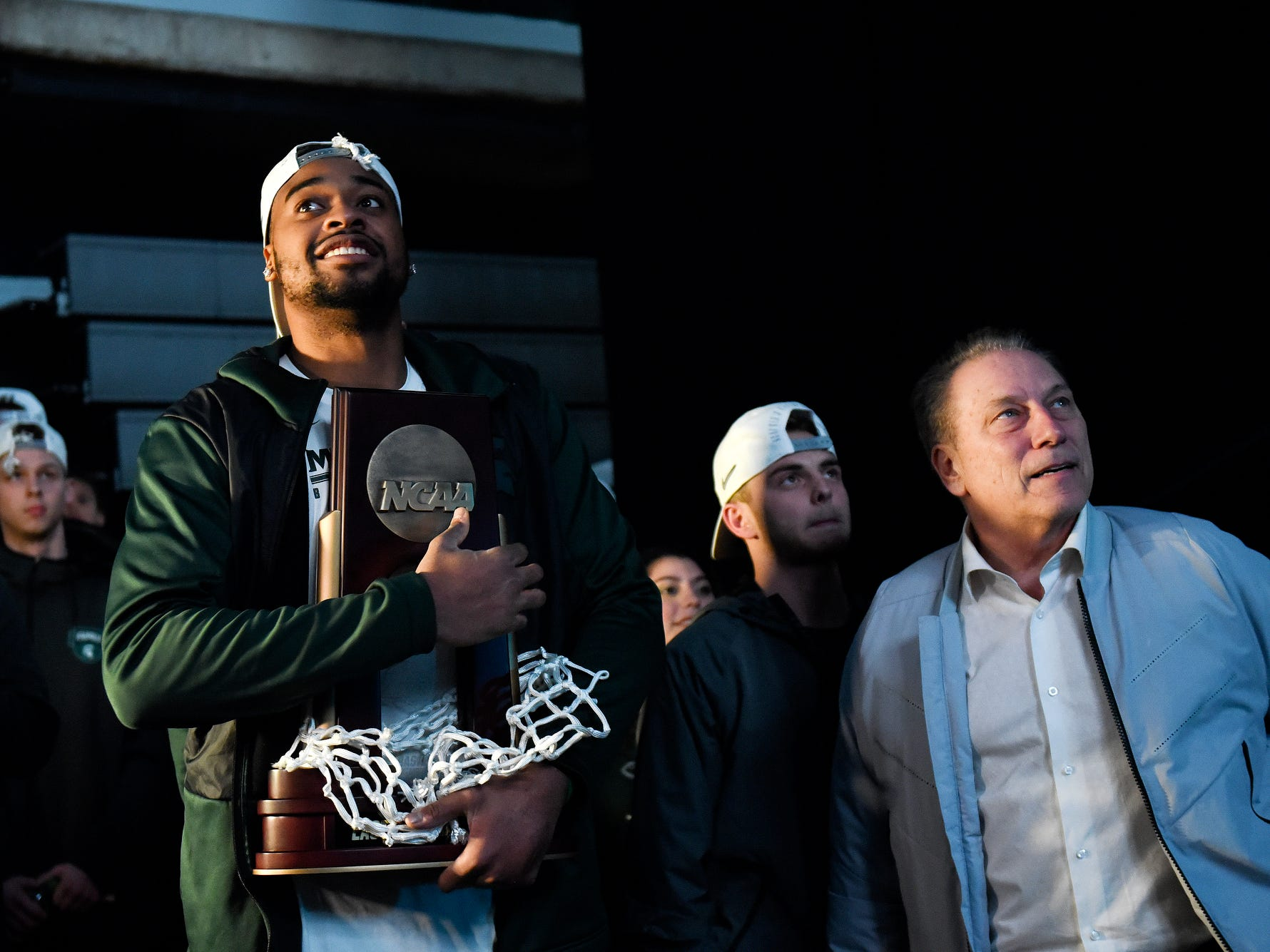 Michigan State's Nick Ward, left, holds the East Regional Championship trophy while he and head coach Tom Izzo, right, watch a video tribute to the team backstage during a rally after MSU's victory over Duke on Sunday, March 31, 2019, at the Breslin Center in East Lansing. The Spartans beat Duke 68-67 to reach the Final Four.