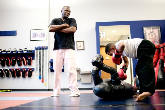 Boxing trainer Kolmarge Harris, left, looks on as student Dwaine Maybin Jr., 7, punches a dummy during a class on Thursday, Feb. 7, 2019, in Old Town Lansing. Harris, a retired professional boxer, offers training for adults and kids with a focus on children who face taunting and bullying like he experienced as a youth.