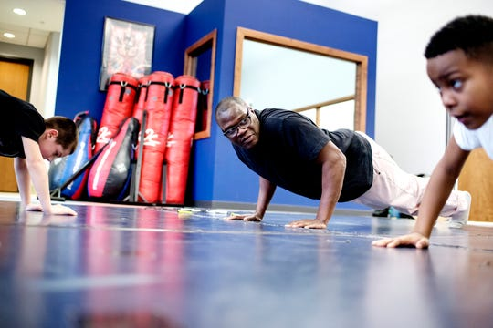 Boxing trainer Kolmarge Harris, center, does push ups with Enicio Montalvo, 8, left, and Dwaine Maybin Jr., 7, during a class on Thursday, Feb. 7, 2019, at Harris' gym in Old Town Lansing. Harris, a retired professional boxer, offers training for adults and kids with a focus on children who face taunting and bullying like he experienced as a youth.