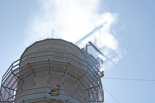 Firefighters made their way to the top of the grain elevator on North Main Street after a fire started Monday afternoon.