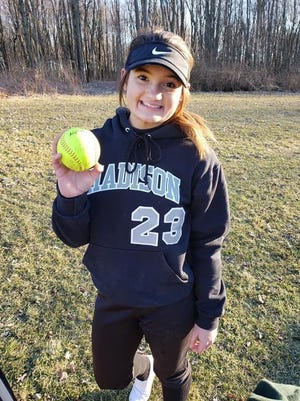 Madison freshman Reagan Hayes poses with her home run ball after she sent the first varsity pitch she ever saw soaring over the fence.