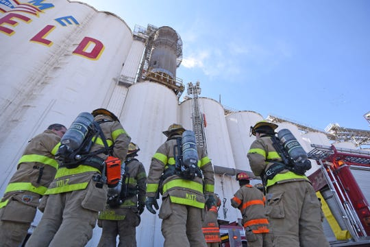 Mansfield firefighters wait for the ladder to bring hoses  and gear Monday afternoon after the grain elevator bearing the Welcome to Mansfield message caught fire.