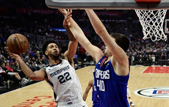 Memphis Grizzlies guard Tyler Dorsey, left, shoots as Los Angeles Clippers center Ivica Zubac defends during the first half of an NBA basketball game, Sunday, March 31, 2019, in Los Angeles. (AP Photo/Mark J. Terrill)
