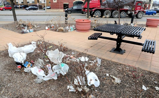 Plastic bags, trash and other litter cover bushes near the corner of West Fond du Lac Avenue and North 21st Street near West North Avenue in Milwaukee on Monday. As of Monday, anyone caught littering in the city will now face a $500 fine.