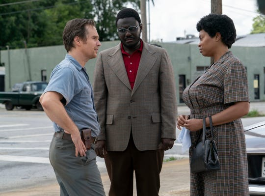 "A Klan leader (Sam Rockwell, left) and a black activist (Taraji P. Jenson) are brought together by a community leader (Babou Ceesay) to figure out school integration in ""The Best of Enemies."""