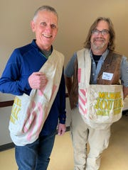 Pat Anas (left) and Mark Koeppl show off the old canvas delivery bags they used as boys decades ago on their Milwaukee Journal paper routes in Whitefish Bay.