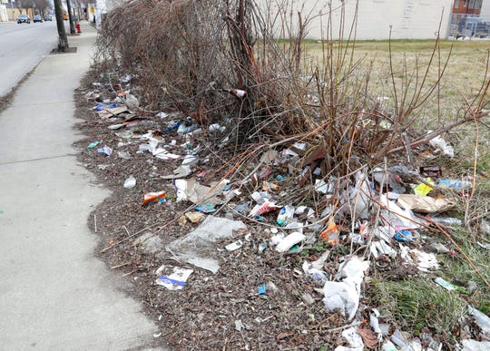 Discarded trash and litter covers an area near a sidewalk near West Hickory Street and West Fond du Lac Avenue in Milwaukee on April 1.