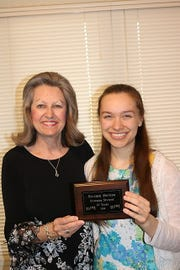 Heather Grace Spencer (right) receivesa plaque from her teacher, Mrs. Caryl Reddick, after receiving 12 years of consecutive superior ratingsat the Junior Festival held each spring in Springfield, Mo.