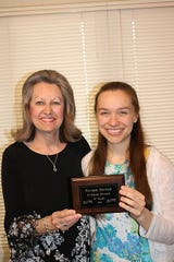 Heather Grace Spencer (right) receives a plaque from her teacher, Mrs. Caryl Reddick, after receiving 12 years of consecutive superior ratings at the Junior Festival held each spring in Springfield, Mo.