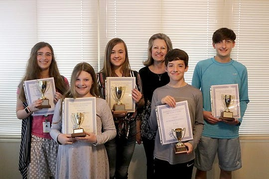 Piano students receiving their first gold cup trophy, which requires at least 3 years (15 pointsare: (first row, from left)McKinley Jackson and Aiden Sanders. Second gold cup recipients, which requires 6 years (30 points total) are: (back row, from left)Trevi Sheaner, Jessalin Meansand Jack Sheaner, pictured with their teacher, Mrs. Caryl Reddick.