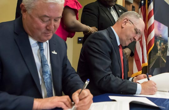 Louisiana Delta Community College Chancellor Dennis Epps, left, signs a memorandum introducing a pilot program to offer job skills to training to Medicad recipients in Northeast Louisiana with Louisiana State Governor John Bel Edwards at the community college in Monroe, La. on April 1.