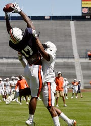 Auburn wide receiver Marquis McClain makes a catch over defender Devin Guice on Saturday, March 30, 2019 in Auburn, Ala.