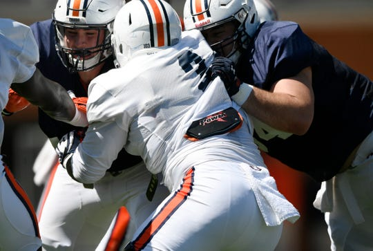Auburn offensive linemen Jack Driscoll (left) and Kaleb Kim (right) block Marlon Davidson (center) during practice on Saturday, March 23, 2019 in Auburn, Ala.