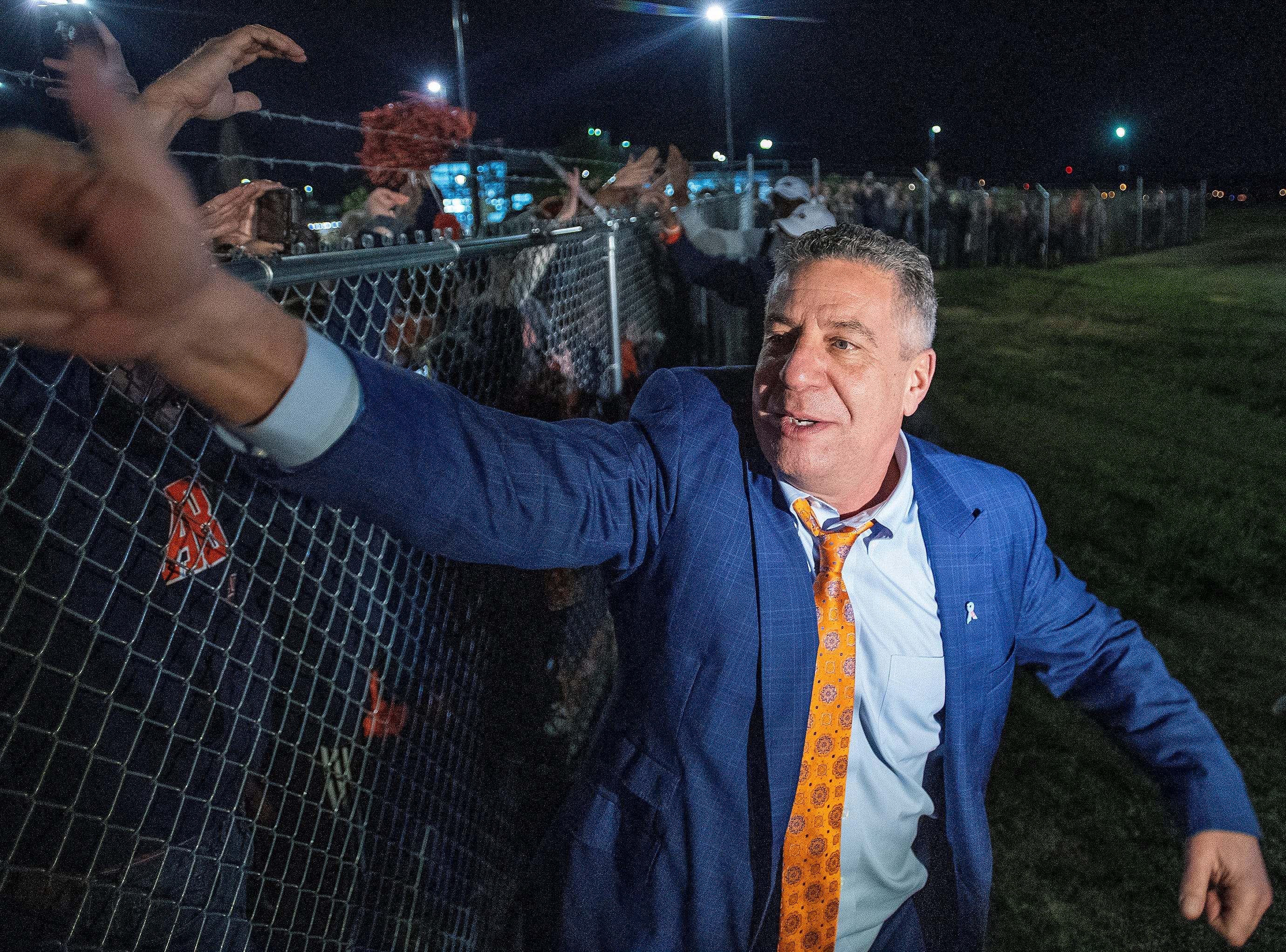 Head coach Bruce Pearl greets fans gathered along the fence line as the Auburn men's basketball team arrives at the Montgomery, Ala., airport on Sunday evening March 31, 2019 after defeating Kentucky in Kansas City to advance to the NCAA Basketball Final Four next weekend.