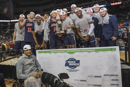 Auburn players, including the injured Chuma Okeke (left) pose after winning the Midwest Region of the NCAA Tournament on March 31, 2019, in Kansas City.
