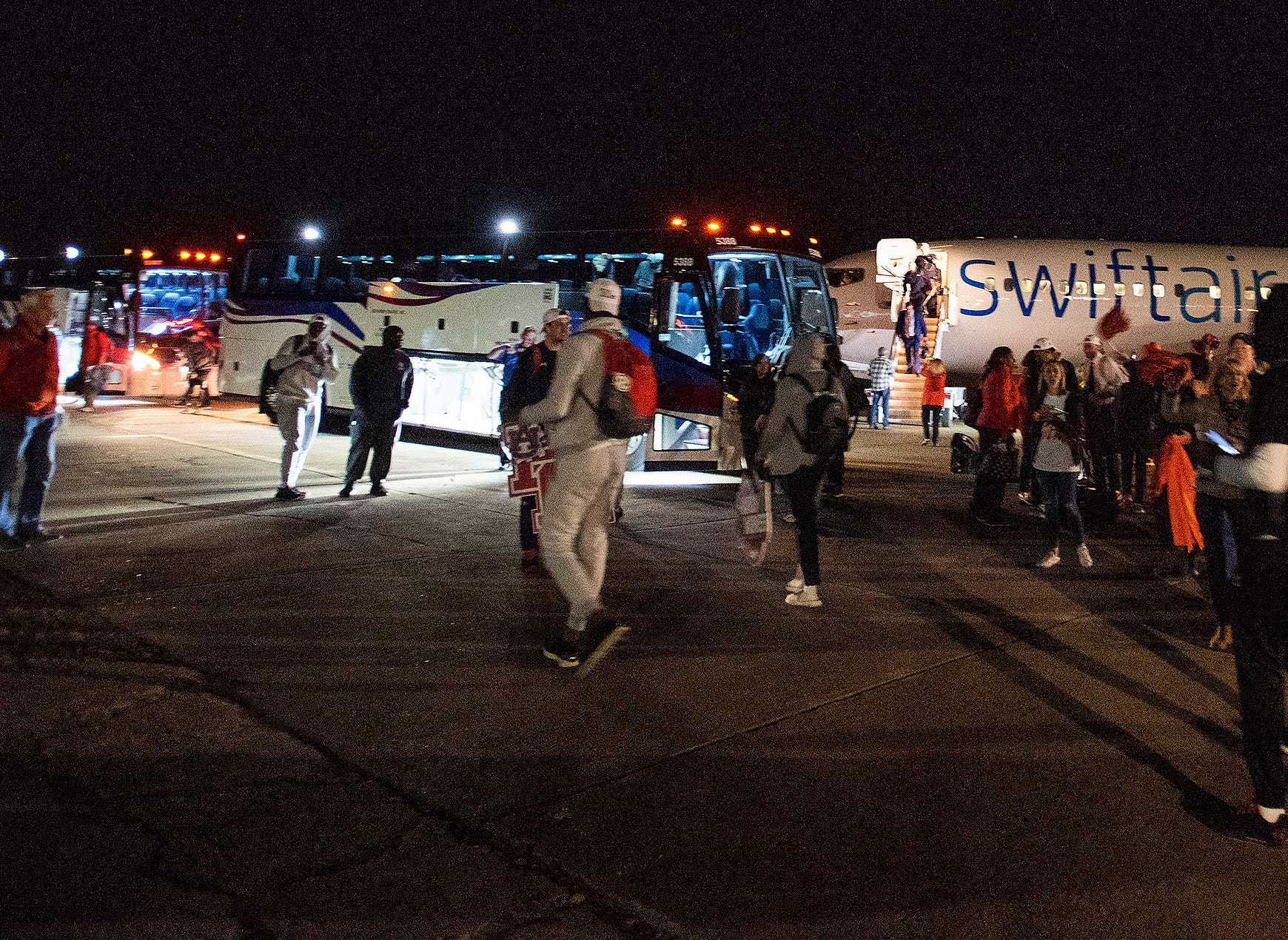 Players load onto buses as the Auburn men's basketball team arrives at the Montgomery, Ala., airport on Sunday evening March 31, 2019 after defeating Kentucky in Kansas City to advance to the NCAA Basketball Final Four next weekend.