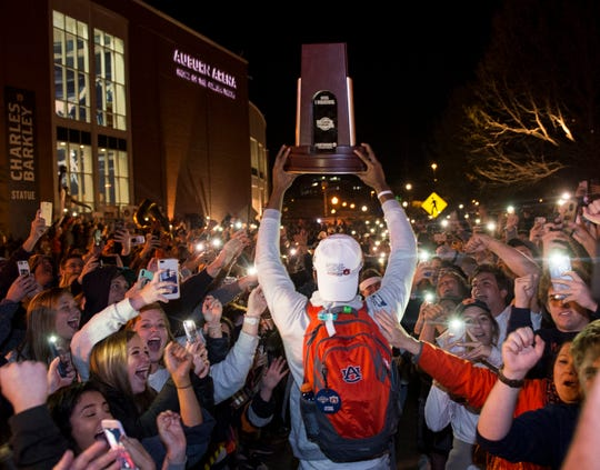 Auburn forward Anfernee McLemore (24) holds up the Midwest Regional Championship trophy as fans welcome back the Auburn basketball team after the team's Elite Eight win outside Auburn Arena in Auburn, Ala., on Sunday, March 31, 2019.
