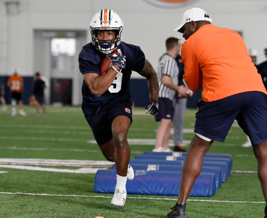 Auburn running backs coach Cadillac Williams (right) coaches Kam Martin through drills during practice in Auburn, Ala.