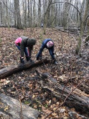 Kids from Red-Tail Conservancy's Wildlife Warrior program look for salamanders in the woods.