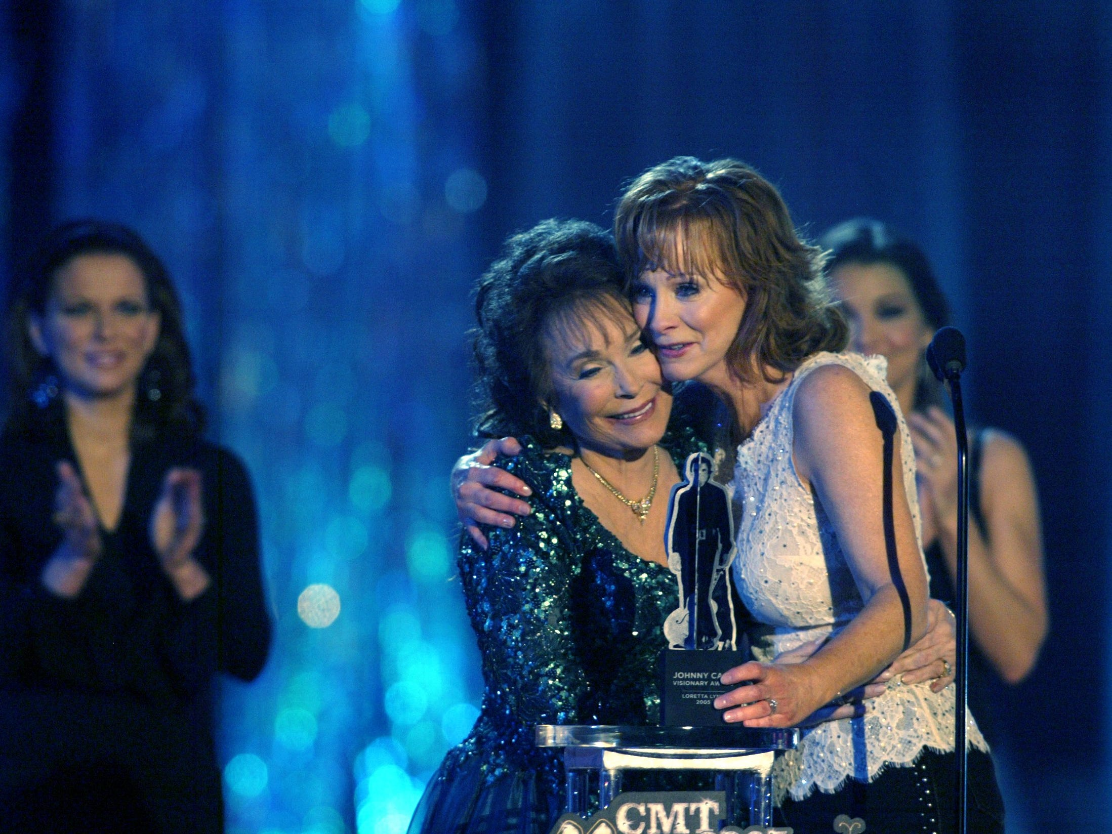 Reba McEntire, right hugs Loretta Lynn while presenting the Johnny Cash Visionary Award to Lynn during the CMT Country Music Awards show at the Gaylord Entertainment Center April 11, 2005.