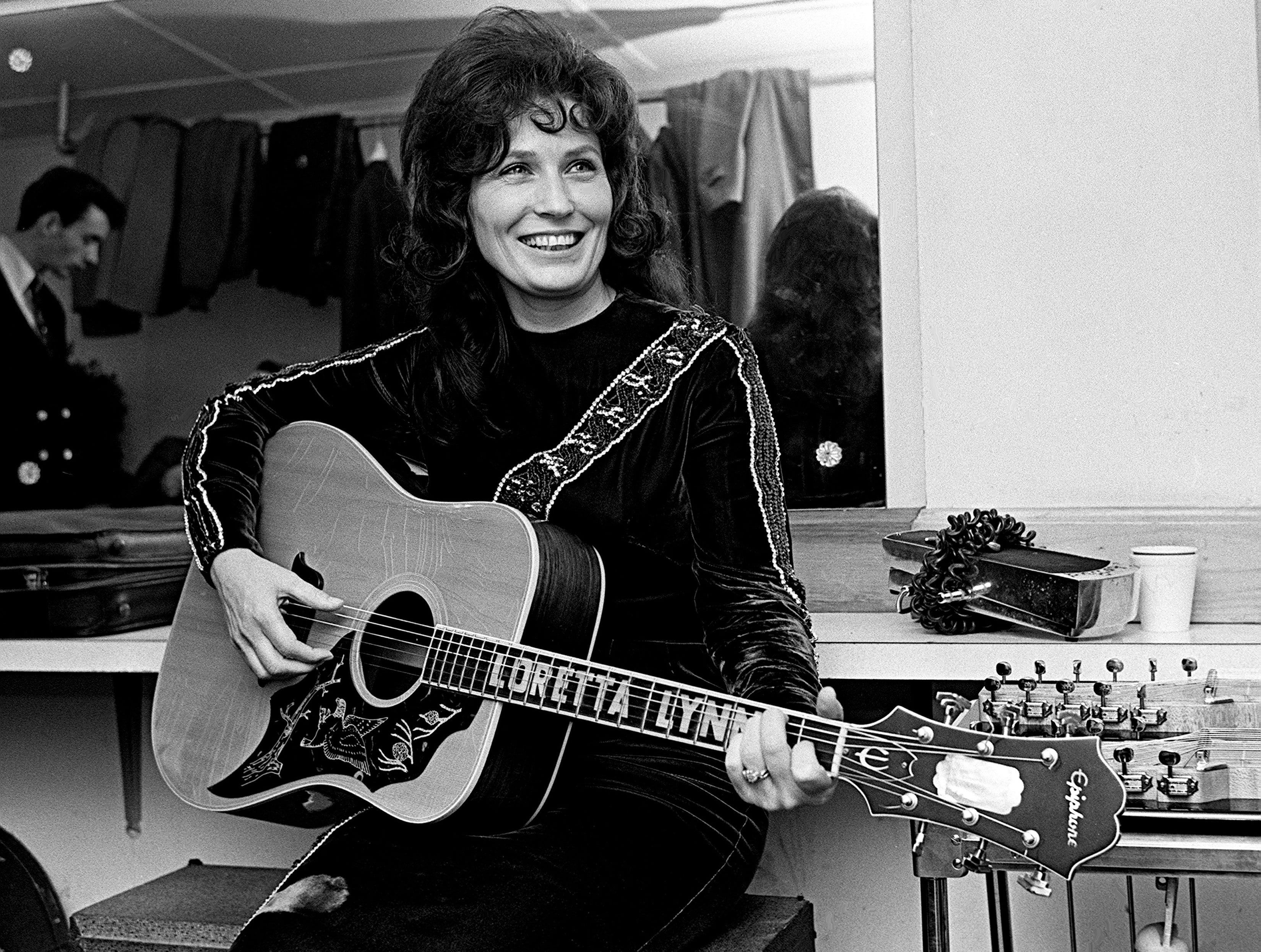 Loretta Lynn warms up in the dressing room at the Ryman Auditorium before going on stage for a Saturday night Grand Ole Opry show Dec. 10, 1966.