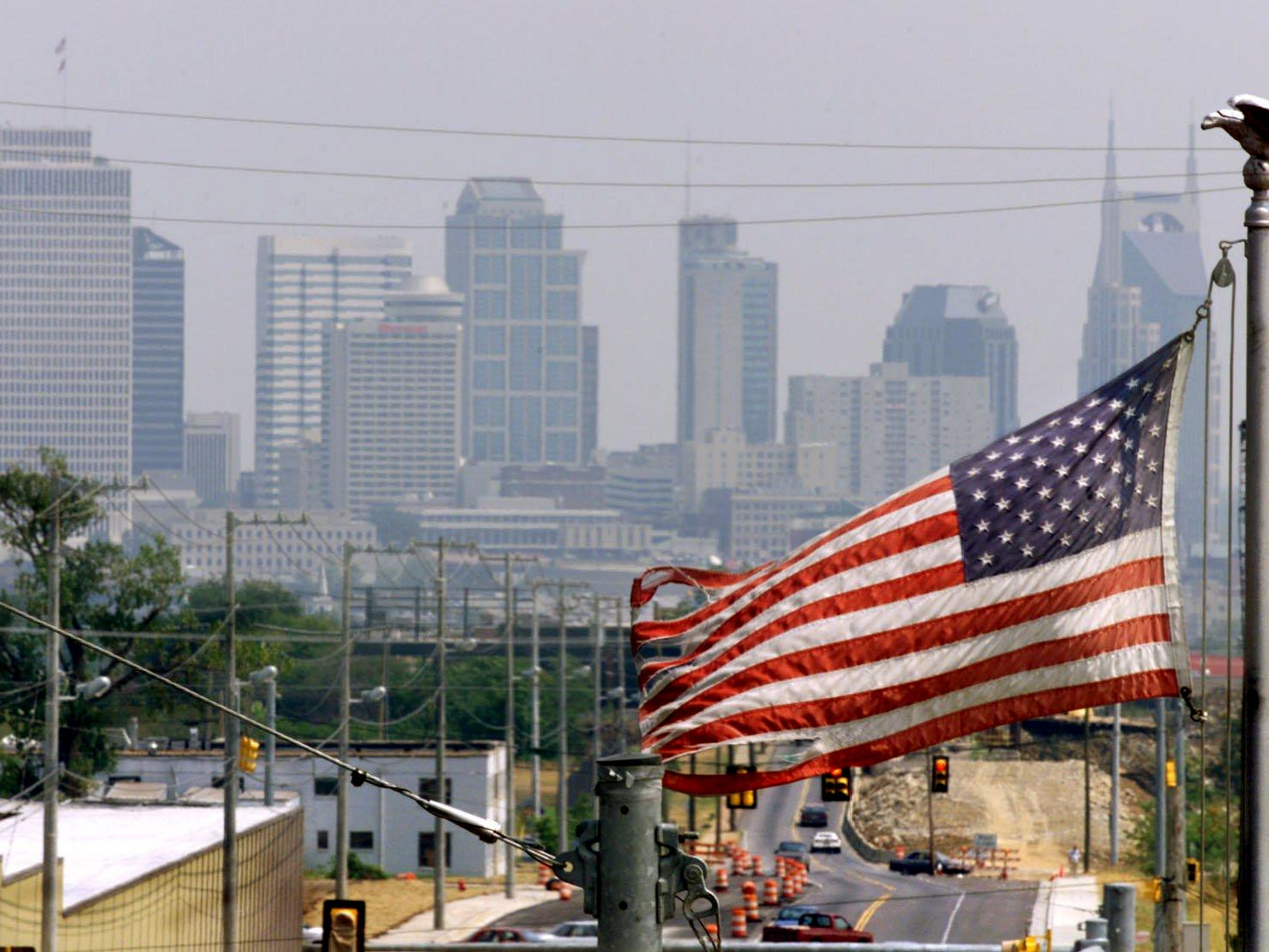 An American flag on Charlotte Avenue near I-440 frames the hazy Nashville skyline on Aug. 24, 1999.